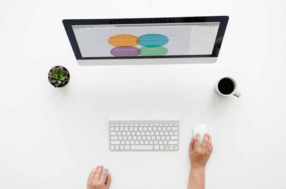 silver imac on white surface near apple keyboard and magic mouse held by human hand